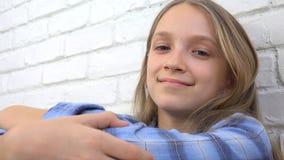 Den fundersamma barnståenden som ler ungeframsidan som ser blondinen, borrade in camera flickan arkivfoto