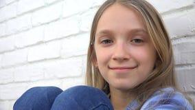 Den fundersamma barnståenden som ler ungeframsidan som ser blondinen, borrade in camera flickan royaltyfri foto