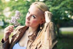 Den fundersamma blonda kvinnan med en filial av lila wolks parkerar in royaltyfri foto