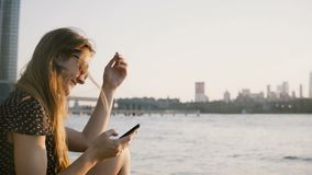 Den fundersamma Caucasian flickan i solglasögon som använder smartphonesamkvämmen, knyter kontakt app som tycker om fantastisk so stock video