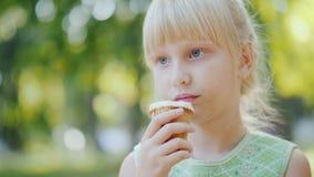 Den fundersamma flickan 6 gamla år äter glass i parkera Ferie i sommar och semestrar Fotografering för Bildbyråer