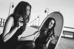 Den fundersamma kvinnan ser reflexion i spegel royaltyfri bild