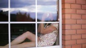 Den fundersamma ledsna brunettmitt åldrades kvinnan i pyjamas som sitter på fönsterbrädan arkivfilmer