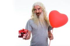 Den fundersamma lyckliga pensionären uppsökte mannen som ler, medan rymma rött honom arkivfoton