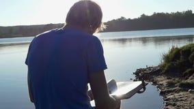 Den fundersamma mannen ser hans photoalbum på en sjöbank lager videofilmer