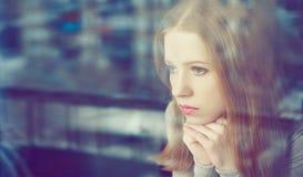 Den fundersamma sorgsenhetflickan är ledsen på fönstret Royaltyfri Bild