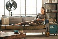 Den fundersamma stilfulla kvinnan sitter på soffa- och innehavminnestavlan royaltyfria bilder
