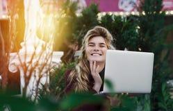 Den fundersamma unga kvinnan i exponeringsglas genom att anv?nda en dator som sitter p? en b?nk i en stad, parkerar Begreppet av  arkivfoton