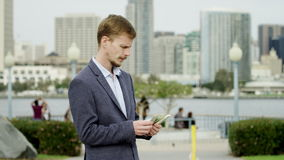 Den fundersamma unga mannen räknar pengar på en gata lager videofilmer