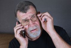 Den fundersamma vuxna mannen lyssnar på mobiltelefonen Arkivbilder