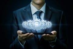 Den funktionsdugliga mekanismen av kugghjul med insidan för valutaenheter hänger ovanför apparaten i affärsmannens händer royaltyfri bild