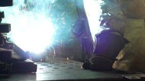 Den funktionsdugliga welderen på fabriken i en skyddande dräkt svetsar delen, welderen gör delen, produktionen, närbild arkivfilmer
