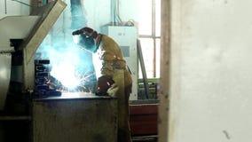 Den funktionsdugliga welderen på fabriken i en skyddande dräkt svetsar delen, welderen gör delen, produktionen, welder lager videofilmer