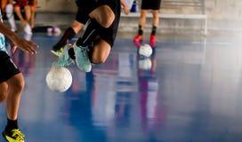 Den Futsal spelaren hoppar med fälla och kontrollerar bollen för fors till royaltyfri bild