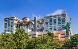 Den futuristiska Fuji TVbyggnaden och statyn av Liberty Replica i Odaiba Tokyo Royaltyfri Bild