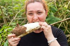 Den fylliga kvinnan som tuggar en kassava, rotar Royaltyfri Fotografi