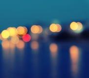 Den fyrkantiga bilden av suddiga ljus för en stad med bokeheffekt reflekterade på vatten Arkivbild
