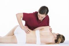 Den fysiska terapeuten gör ryggrads- mobilisering till kvinnan Royaltyfri Bild