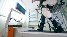 Den fysiskt utmanade personen utbildar hans ben på ett rinnande spår Elektroniskt medicinskt robotic för rehabilitering stock video