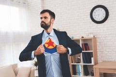 Den gömda superheroen leder ett dubbelt liv Han är i en dräkt, men under honom lögner kläderna av en superhero Arkivbild