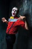 Den galna clownen som rymmer en kniv på dack för den grymma säger miniatyrreaperen halloween för kalenderbegreppsdatumet lyckliga Arkivfoton