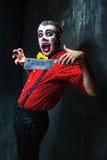 Den galna clownen som rymmer en kniv på dack för den grymma säger miniatyrreaperen halloween för kalenderbegreppsdatumet lyckliga Royaltyfri Foto