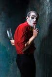 Den galna clownen som rymmer en kniv på dack för den grymma säger miniatyrreaperen halloween för kalenderbegreppsdatumet lyckliga Royaltyfria Foton