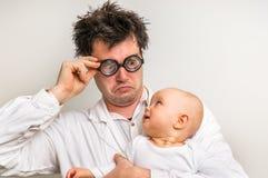 Den galna doktorn med nyfött behandla som ett barn i hans händer Arkivbild