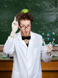 Den galna forskaren med ett äpple på hans huvud visar pekfingret, medan räcka den molekylära modellen Royaltyfria Bilder