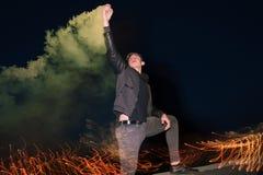 Den galna manliga fanen med rök bombarderar på natten Arkivfoto