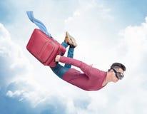 Den galna mannen i skyddsglasögon flyger i himlen med en röd resväska med att fladdra kläder Begreppet är snabbare på semester royaltyfri bild
