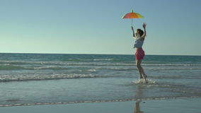 Den galna roliga kvinnan i rosa färgkjol med solglasögon är köra och hoppa på stranden Semestern har kommit lyckliga hopp för fli stock video