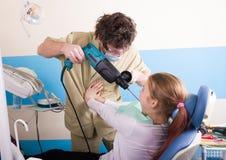 Den galna tandläkaren behandlar tänder av den olyckliga patienten Patienten skrämmas Arkivbilder