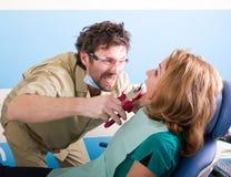 Den galna tandläkarepatienten på tandläkaren, patienten skrämmas Arkivbilder