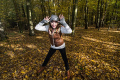 Den galna unga kvinnan gör gyckel i höstskogen Royaltyfria Bilder