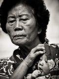Den gamla äldre kvinnan bär behandla som ett barn på gatan av kineskvarteret, Singapore arkivfoton