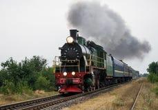 Den gamla ångalokomotivet reser vid stången Arkivfoton