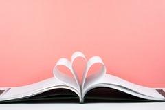 Den gamla öppna inbunden bokboken, sida dekorerar in i en blommaform för förälskelse i valentin` s förälskelse med öppen bokhjärt Arkivbild
