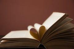 Den gamla öppna inbunden bokboken, sida dekorerar in i en hjärtaform för förälskelse i valentin` s förälskelse med öppen bokhjärt arkivfoto