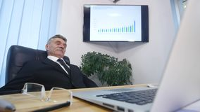 Den gamla affärsmannen lutade tillbaka i hans kontorsstol, ler han och att dagdrömma arkivfilmer