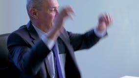 Den gamla affärsmannen lutade tillbaka i hans kontorsstol, ler han och att dagdrömma stock video