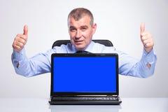Den gamla affärsmannen visar upp bärbara datorn och tummar Royaltyfria Bilder