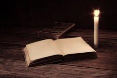 Den gamla antikviteten öppnade boken med bränningstearinljuset nära på trätabellen arkivbild