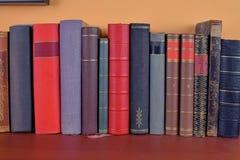 Den gamla antikviteten bokar bakgrund De forntida böckerna på en apelsin- och bordeauxbakgrund royaltyfri fotografi