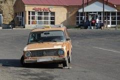 Den gamla armeniska taxien med det brutna hjulet royaltyfria foton