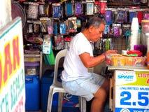 Den gamla asiatiska mannen som arbetar i mobiltelefonreparation, shoppar Arkivbild