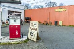 Den gamla bilreparationen shoppar med en bensinstation som annonserar för billiga gummin arkivbilder