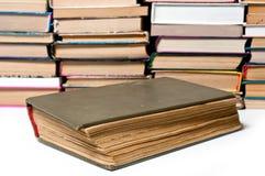 Den gamla boken är ett stort ett skjutit stort på bakgrunden av andra böcker arkivbilder