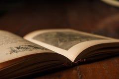 Den gamla boken av fablar öppnade på den gamla lantliga trätabellen, numrerar en i tecken på baksidan Bakgrund med mjuk suddighet Fotografering för Bildbyråer