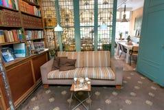 Den gamla boken shoppar med antika fönster, soffan och tabeller för kaffe och lunch av avläsare Royaltyfria Foton